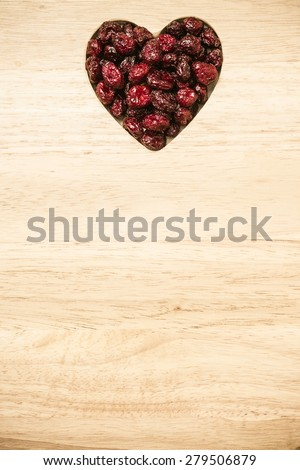 Healthy high fiber food, organic nutrition. Dried cranberries cranberry fruit in shape of heart on wooden surface background  - stock photo