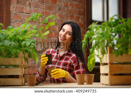 Healthy hobby. Portrait of a beautiful female holding a seedling and a pot in her hands looking to the camera smiling joyfully. - stock photo