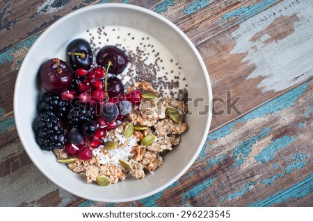 Healthy home made oatmeal porridge muesli with kefir yogurt and topped with blackberries, cherries,pomegranate, pumpkin and chia seeds. Served on a rustic wooden table.