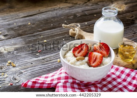 Healthy homemade breakfast. Fresh milk porridge with garden ripe strawberries in white ceramic bowl on a simple wooden dark background with a bottle of honey and cream. selective focus - stock photo