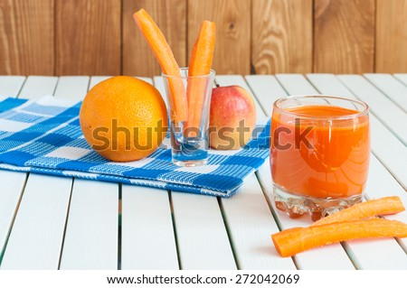 Healthy homemade carrot juice in glass and fresh carrot, apple, orange on light wooden background. Weight loss, healthy food, diet and detoxification - stock photo