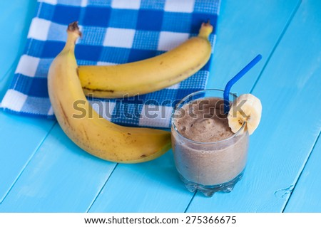 Healthy homemade Chocolate banana smoothie in glass and fresh bananas on light wooden background. Weight loss, healthy food, diet and detoxification - stock photo