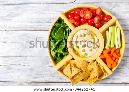 Healthy homemade delicious spicy hummus with baby carrots, celery sticks, spinach, ginger, sliced lime, virgin olive oil, pine nuts and pita bread, top  view - stock photo