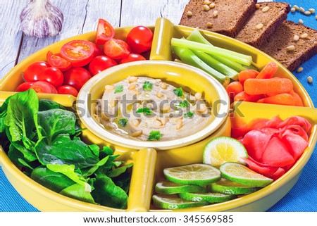 Healthy homemade delicious spicy hummus with baby carrots, celery sticks, spinach, ginger, sliced lime, virgin olive oil, pine nuts and bread - stock photo