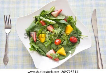 Healthy homemade fresh salad made with spring greens, fruits and vegetables. Arranged in a white bowl on a dining table next to a window. - stock photo