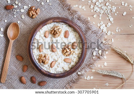 Healthy homemade oatmeal porridge with nuts. Perfect vegetarian diet breakfast concept. Vintage wooden table background. Rustic style and natural light - stock photo