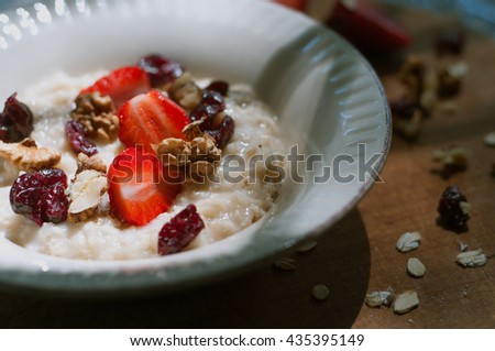 healthy homemade vegan breakfast. oatmeal bowl with strawberries dried fruits oat milk and nuts. rustic style - stock photo