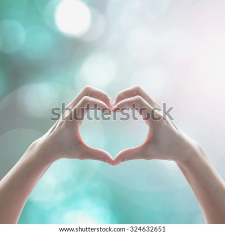 Healthy human hand in heart shape showing love friendship on blurred abstract cool blue green sky color bokeh background: Global eco environment CSR natural resource awareness/ concept/ campaign/ idea - stock photo