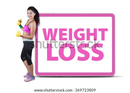 Healthy indian woman holding two dumbbells and leans on a billboard with text of weight loss - stock photo