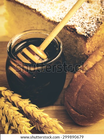 Healthy jar of honey with bakery products on wooden background. - stock photo
