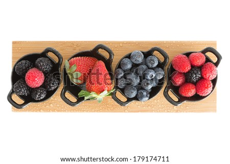 Healthy juicy autumn or fall strawberries, blueberries,. blackberries, and raspberries displayed in individual ceramic ramekins on a wooden board isolated on a white background, view from above - stock photo