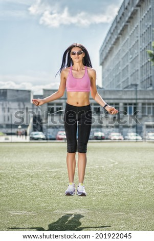Healthy jumping up and slim figure. Young and charming woman in sunglasses and sportswear standing on the football field and jumping rope on the front view - stock photo