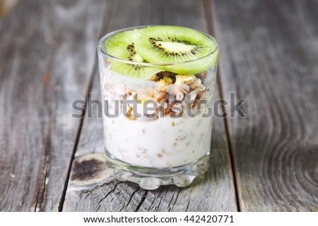 Healthy layered dessert with cream, muesli, on wooden background. Healthy breakfast - health and diet concept, close up. - stock photo