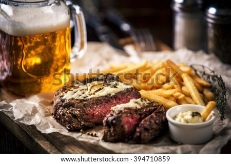 Healthy lean grilled medium-rare steak with french fries, beer - stock photo