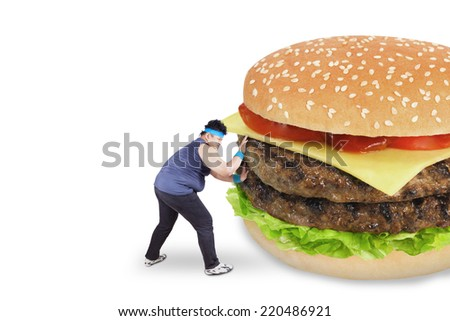 Healthy life concept. Overweight man refused to eat a big burger and pushing it - stock photo