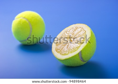Healthy life concept with half lemon and half tennis ball on blue background.Focus in the foreground. - stock photo