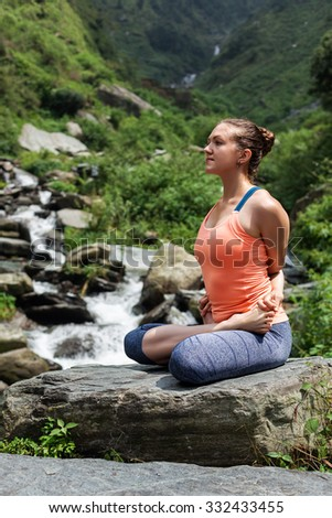 Healthy life exercise concept - Young sporty fit woman doing yoga - meditating in Baddha Padmasana (Bound Lotus Pose) outdoors at tropical waterfall