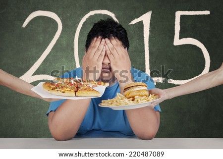 Healthy life plan. Overweight person avoiding to eat junk food in 2015 - stock photo