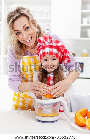 Healthy life - woman and little girl pressing fresh orange juice - stock photo