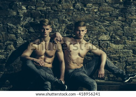 Healthy lifestyle and bodybuilding. Twin brothers young sensual serious with bare chest in jeans pose outdoor