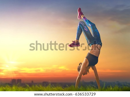 healthy lifestyle and sport concepts woman in fashionable sportswear is doing exercise on nature