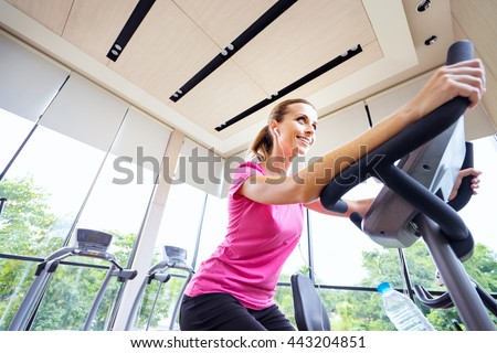 Healthy lifestyle and sport. Pretty young woman exercising in gym. - stock photo