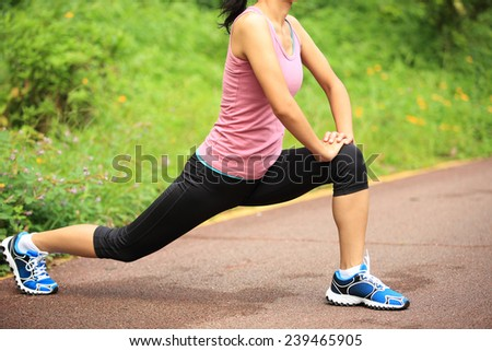 healthy lifestyle asian woman runner stretching legs before running  - stock photo