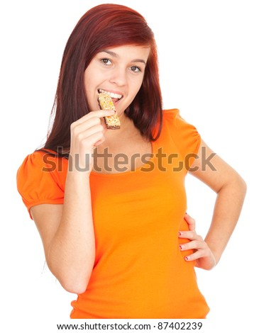 healthy lifestyle, beautiful young girl eating granola bar, white background - stock photo