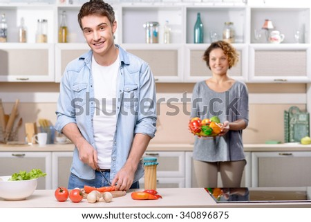 Healthy lifestyle. Cheerful delighted smiling husband holding knife and cooking with his wife standing in the background and holding bowl with vegetables - stock photo