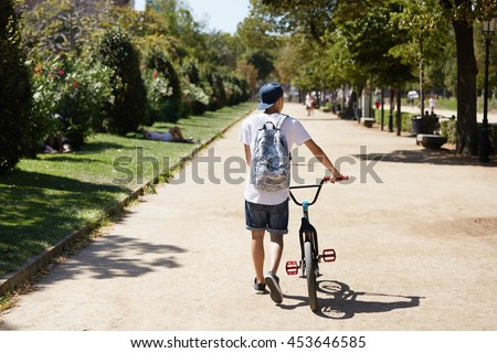 Healthy lifestyle concept. Back view of teenage boy in street wear, carrying backpack and walking with his BMX bike beside him holding it by the handlebar along green lane on sunny summer day - stock photo