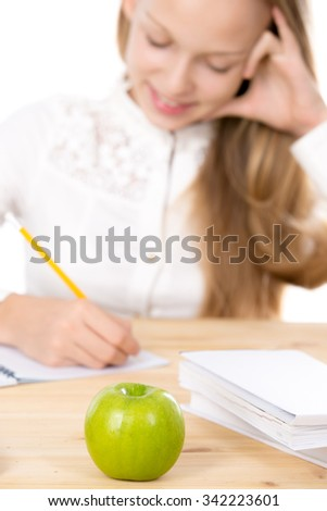Healthy lifestyle concept, cheerful beautiful casual caucasian schoolgirl, sitting at the desk, doing schoolwork, busy with studying, focus on green apple on foreground, studio shot, white background - stock photo