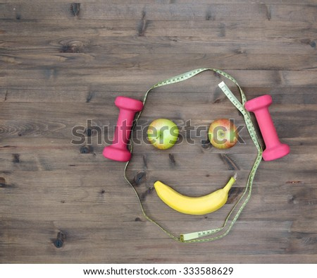 Healthy lifestyle concept. colored Apples measuring tape dumbbells banana look like face on  wooden table  - stock photo
