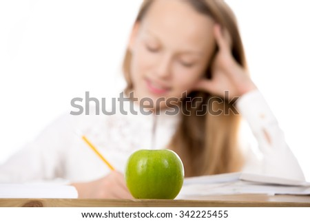 Healthy lifestyle concept, happy beautiful casual caucasian girl, sitting at the desk, doing homework, studying, focus on green apple on table, isolated studio shot, white background - stock photo
