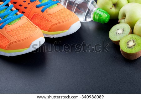 Healthy lifestyle concept. Sport shoes, apples, kiwi, bottle of water on dark background. Sport equipment. Copyspace. Selective focus - stock photo