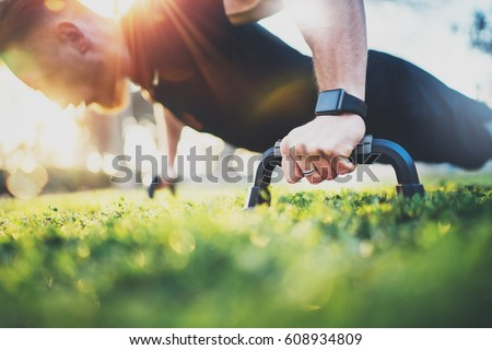 Healthy lifestyle concept.Training outdoors.Handsome sport man doing crossfit pushups in the park on the sunny morning. Blurred background