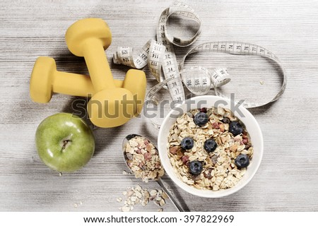 healthy lifestyle concept with fresh muesli and fruits on a wooden table - stock photo