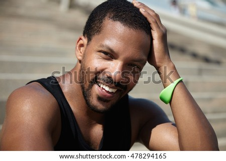 Healthy lifestyle concept. Young African runner having break sitting against blurred background of concrete stairs, after morning training outdoors, looking and smiling at camera touching his head