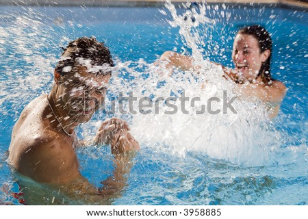 Healthy lifestyle: couple having fun at the swimming pool - stock photo