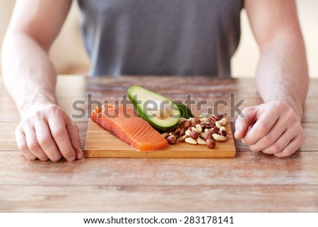 healthy lifestyle, diet and people concept - close up of male hands with food rich in protein on cutting board on table - stock photo