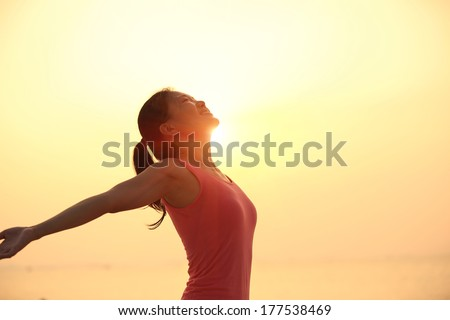 healthy lifestyle fit woman open arms under the sunrise at sea  - stock photo