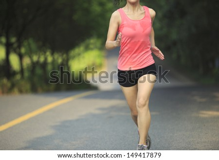 healthy lifestyle fit woman runner running at forest driveway - stock photo