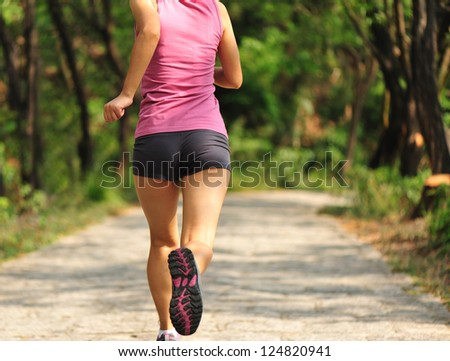 healthy lifestyle fitness sporty  woman runner running in forest trail - stock photo