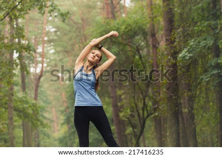 healthy lifestyle fitness sporty woman stretching before run early in the morning in forest area - stock photo