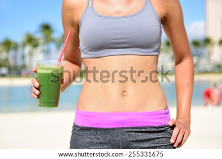 Healthy lifestyle fitness woman drinking green vegetable smoothie juice after running exercise.  Close up of smoothie and stomach. Healthy lifestyle concept with fit female model outside on beach. - stock photo