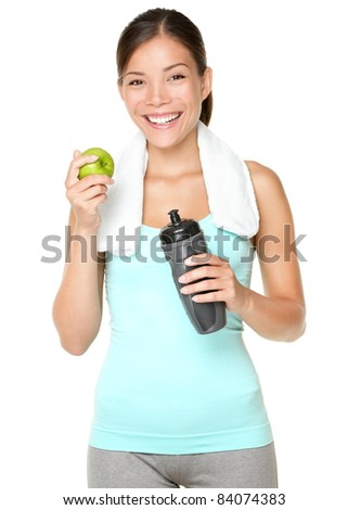 Healthy lifestyle - fitness woman eating apple smiling happy looking at camera. Pretty mixed race Caucasian Asian woman isolated on white background. - stock photo