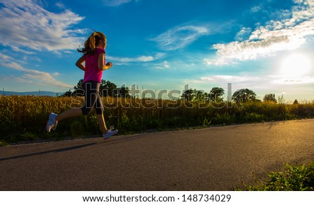 Healthy lifestyle - girl jumping, running outdoor  - stock photo