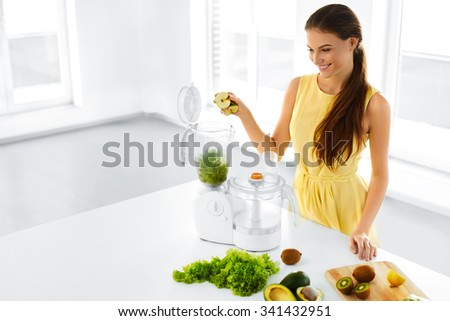 Healthy Lifestyle. Happy Smiling Vegetarian Woman Making Green Detox Vegetable Smoothie With Blender Home In Kitchen. Healthy Eating, Diet, Raw Food Concept. - stock photo
