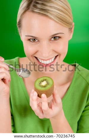 Healthy lifestyle - happy woman holding kiwi and teaspoon on green background