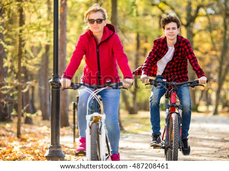 Healthy lifestyle - people riding bicycles in city park ( focus on boy )