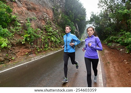 Healthy lifestyle people running on country road exercising. Runners jogging on mountain road training for marathon. Asian woman and Caucasian man wearing waterproof sports clothing for wind and rain. - stock photo